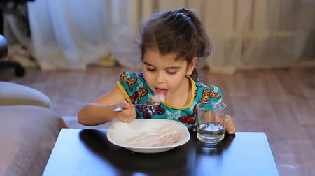 búzadara : Girl distracted while eating. Little girl eats porridge. Looking away