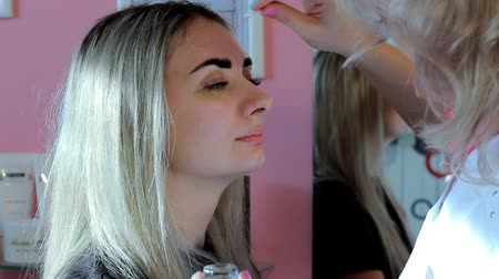 gençleştirme : Cosmetologist corrects a contour of eyebrows when painting.