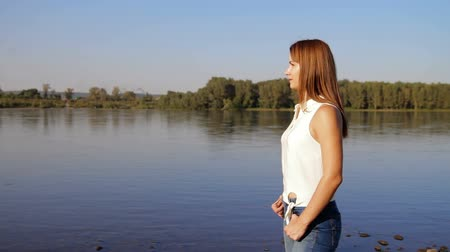 idílio : woman standing on the river shore. the beautiful girl with a slim figure admires a landscape