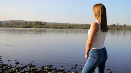 zadek : woman standing on the river shore. the beautiful girl with a slim figure admires a landscape