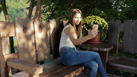 itself : woman takes a selfie against the background of flowers. woman sits on a wooden shop near flowers. Stock Footage