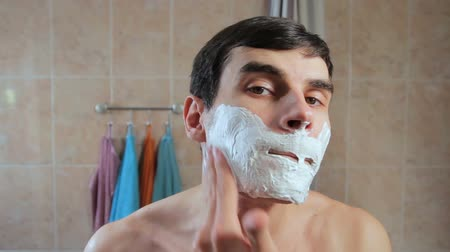 hand on chin : Man gets shaving foam on the face. The guy starts to shave in front of a mirror. looking at herself.
