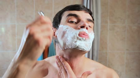 shaving foam : A man shaves his face in the foam with a razor. Guy shaves in front of a mirror