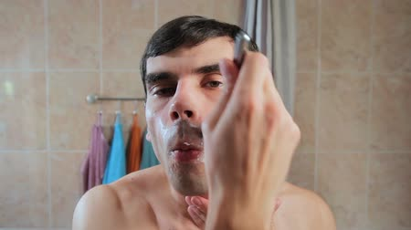 shaves : A man shaves his face in the foam with a razor. Guy shaves in front of a mirror