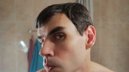 hand on chin : A man checks the quality of the shave. Examines his face in the mirror. Stock Footage