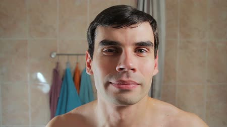 towel white : Portrait of a handsome clean-shaven men standing in the bathroom. Boy smiling standing in front of the mirror in the bathroom Stock Footage