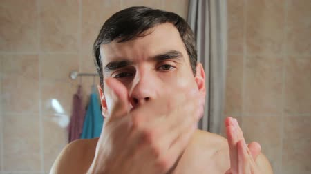 itself : A man smears the face lotion after shaving. Guy sting the face after using the aftershave. Stock Footage