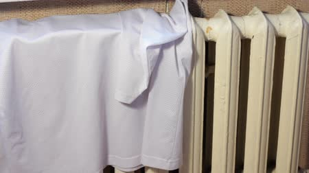 male hand broadcast wet clothes on the radiator to dry. Drying washed clothes. A man does household chores