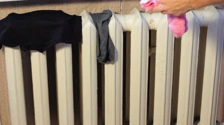 prát : male hand broadcast wet clothes on the radiator to dry. Drying washed clothes. A man does household chores