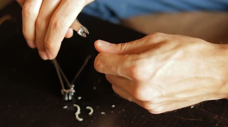 Mens hands cut off rough skin around the nail. To remove the cuticle with the help of tweezers. mens manicure