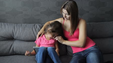 Mother with a child use a tablet sitting on the sofa. Woman tickles baby sitting on couch. Spoiling during training. 影像素材
