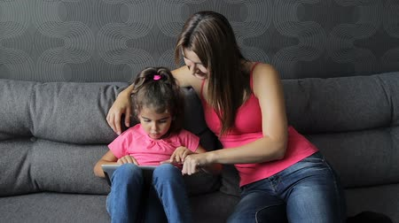 woman with a child use a tablet sitting on the couch. The girl presses her mothers finger into the tablet. Fun during training.