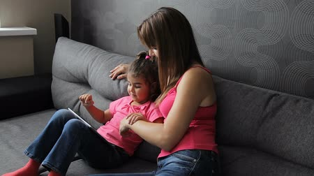 woman with a child use a tablet sitting on the couch. Mother with a child use a tablet sitting on the sofa 影像素材