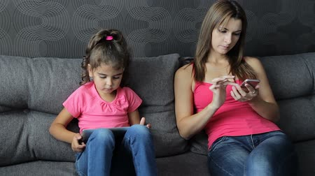 Modern Family Values. slavery of electronics. Mother with a child use a tablet and smartphone sitting on the sofa