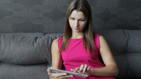 Woman in dress sitting with tablet on the couch. Girl working on a tablet computer sitting on the sofa