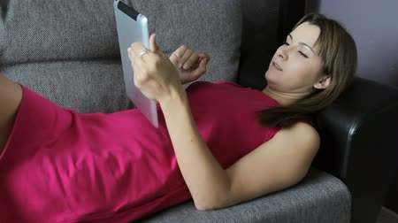 Woman in a dress lies with tablet on the sofa. Lie on your back. Lovely woman at home