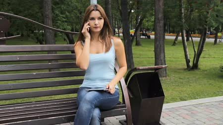 girl talking on the smartphone in city park. woman sitting on a bench with gadgets in the Park.