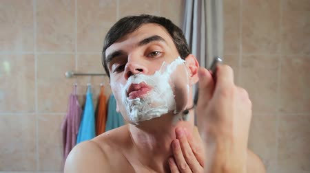 sörte : A man shaves his face in the foam with a razor. Guy shaves in front of a mirror