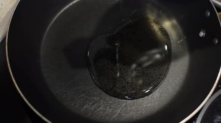 induction cooker : pour the oil into a frying pan. clouseup Stock Footage