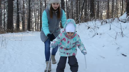nordic countries : Girl child is learning to ski. She slowly slides on skis in soft fresh snow. Beautiful day in the winter forest. Woman teaches a child to ski. Walk in the snowy forest