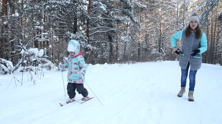 Girl child is learning to ski. She slowly slides on skis in soft fresh snow. Beautiful day in the winter forest. Woman teaches a child to ski. Walk in the snowy forest