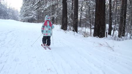 Girl is learning to ski. She slowly slides on skis in soft fresh snow. Beautiful day in the winter forest. Walk in the snowy forest