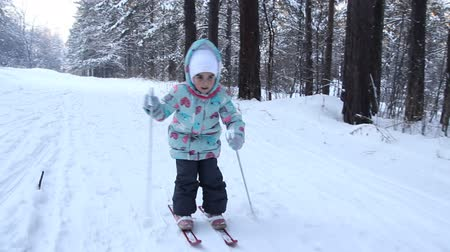 Girl child is learning to ski. She slowly slides on skis in soft fresh snow. Beautiful day in the winter forest. Walk in the snowy forest