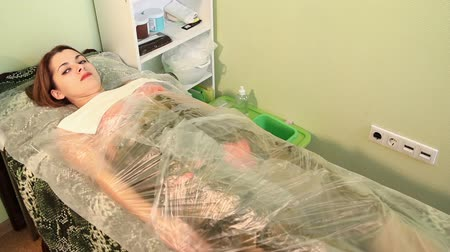 gençleştirme : Seaweed spa. Seaweed wrap. Beautician covers the girl wrapped in seaweed. Anti-aging therapy. Rejuvenescence.