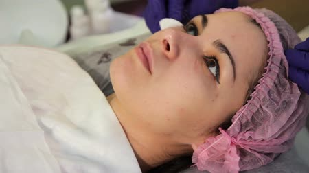 mezoterapia : Disinfection before procedure of mesotherapy. Hands in gloves to wipe the face of a young beautiful woman. Medical procedure rejuvenation.