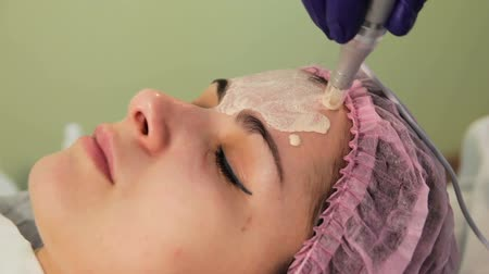 azalan : The young womans face during the procedure closeup. Innovative cosmetic procedure. Medical procedure rejuvenation.