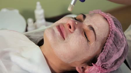 mezoterapia : The woman winces in pain during mesotherapy. Treatment of the nose with an electrical device dermapen.