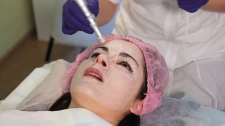 mezoterapia : The girl at the beautician. My nose itches, sneezes soon. The patients face in close-up. A funny scene.