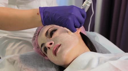 mezoterapia : The woman on the procedure of lightening the skin. The patients face in close-up. The appliance dermapen.