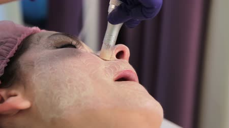 mezoterapia : The girl face close up during the procedure bb glow. Grimace stretching of the skin. Innovative technologies