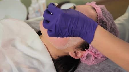 mezoterapia : A gloved hand removes the mask from the womans face. Reddened, irritated skin after mesotherapy. Close-up