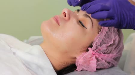 пятна : Cosmetologist applies cream on face of lying woman. Girl in bonnet lying on the session at the beautician. Woman receiving spa treatment