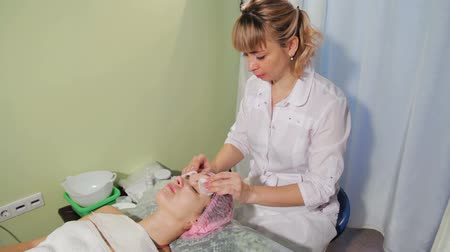lidská hlava : The beautician cleanses the skin with a sponge. Woman is lying on a couch spa salon. Woman receiving spa treatment
