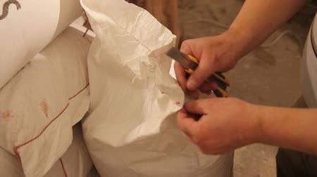 mashing : Mens hands open a bag of malt. Rip. Grinding of malt for producing beer at the brewery. Stock Footage