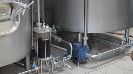 distillation : Craft beer brewing. Filtration of brewed beer. Brewing equipment in action. Tanks for brewing. Stock Footage