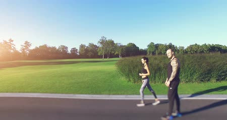 tatuagem : 4K shooting: Young couple running in the park. Athletic attractive people jogging in summer enjoying their healthy lifestyle. Side view. Green meadow and forest in the background