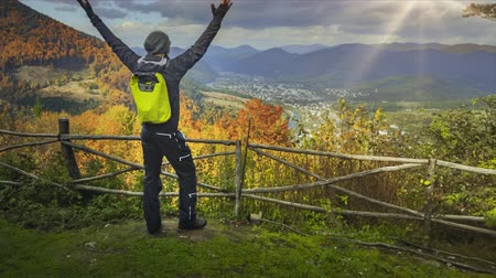 fenómeno : Young man standing on the edge of the cliff and raising his hands up against mountain range and bright colorful autumn forest. Traveler enjoying success and stunning view. Toning filter. Full HD Stock Footage
