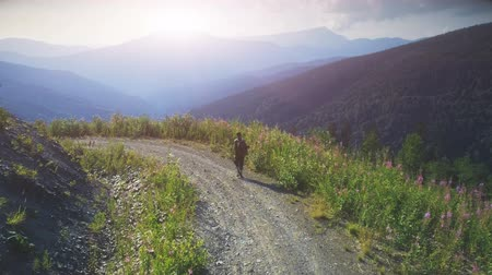 Aerial Drone Flight. Man Traveler with backpack walking sunset mountain road. Travel, Trekking, Lifestyle. Summer vacation activity outdoor. Carpathian mountains range, Ukraine, Europe. 4K slow motion