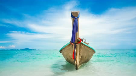 Traditional long tail wooden boat in turquoise crystal water. Ocean waves and blue cloudy sky in the background. Lifestyle, holidays, travel and recreation. Krabi, Thailand. 4k Slow Motion Parallax