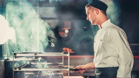 Chef in black apron and hat standing near the brazier whith coals. Cooking beef steak in the interior of modern professional kitchen. Wood burn and air melt from the heat. Blue color filter toning. 4K Slow motion Parallax Vídeos