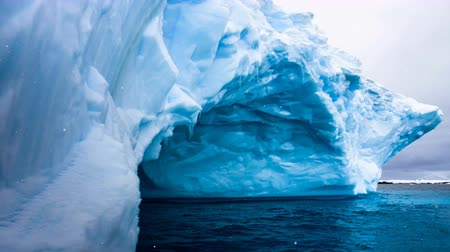 Antarctic Nature. Huge blue iceberg with natural cave inside float in open ocean. Majestic winter landscape, snow fall. Exploring, holiday, recreation, travel. Close up. 4K Slow Motion Parallax Effect