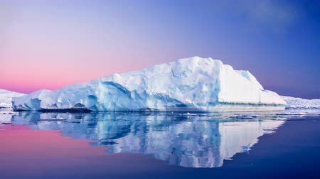 Antarctic Nature. Huge long iceberg with mirror reflection floats in open ocean. Sunset sky in the background. Majestic winter landscape. Explore beauty world, holidays. 4K Slow motion Parallax Effect Vídeos