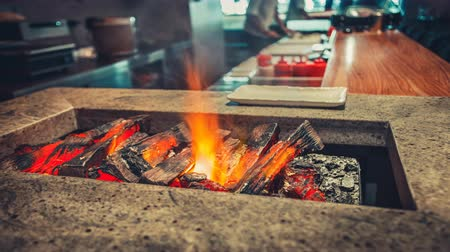 Close-up burning firewood in the interior of the contemporary restaurant kitchen. Modern style design. Wood burn and the air melt from the heat. Bright color filter toning. 4k Slow Motion Parallax
