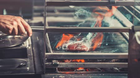 Food concept. Preparing traditional beef steak on barbecue oven in modern restaurant kitchen. Chef stand near brazier whith coals, hand with metal tongs close up. Zoom. 4k Slow Motion Parallax Effect