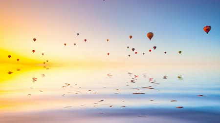 Hot air ballons reflected in ocean water fly in colorful sky at morning sunrise. Majestic summer landscape. Exploring beauty world, holidays and recreation. Travel background. Slow motion 4K footage Vídeos