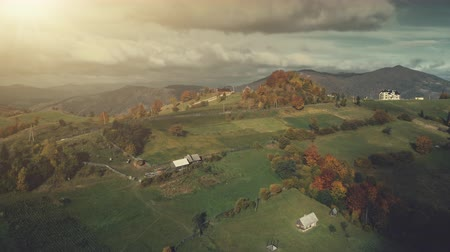Colorful Autumn High Mountain Rural Scene Aerial View. Epic Carpathian Meadow Highlands. Cloudy Sunset Weather. Hill Slope Forest Scene Countryside Cottage. Travel Concept Drone Flight Footage 4K, UHD